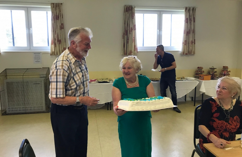 Cllr Helen Manghnani presents Tom Steele with a thank-you Cake